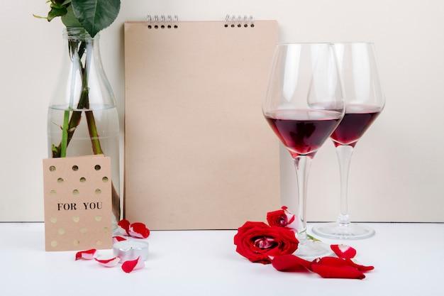 Вид сбоку красных роз в стеклянной бутылке рядом с альбомом для рисования и двумя бокалами красного вина на белом фоне Бесплатные Фотографии