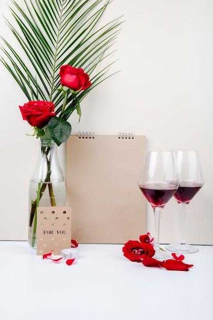 Вид сбоку красных роз с пальмовых листьев в стеклянной бутылке, стоя рядом с альбомом и два бокала красного вина на белом фоне Бесплатные Фотографии