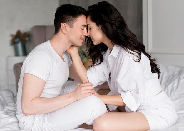 Вид сбоку романтичной пары дома в постели Бесплатные Фотографии