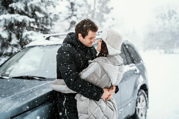 Вид сбоку романтической пары, целующейся в снегу во время поездки Бесплатные Фотографии