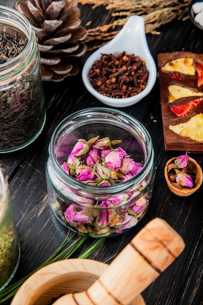 ガラスの瓶、乾燥した紅茶の葉、クローブスパイス、黒い木の果実とチョコレートバーのバラのつぼみの側面図 無料写真