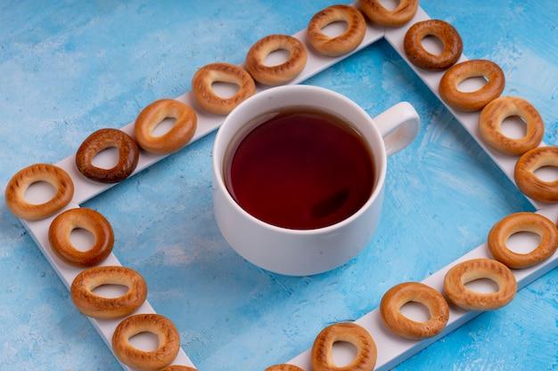 Вид сбоку русских бубликов, подается с чашкой чая на синем Бесплатные Фотографии