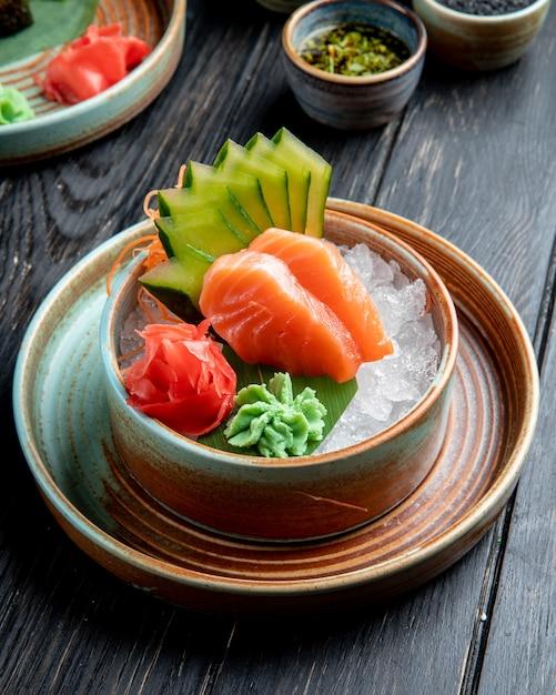 Вид сбоку сашими из лосося с нарезанным огурцом имбирем и соусом васаби на кубиках льда в миске на деревянном столе Бесплатные Фотографии