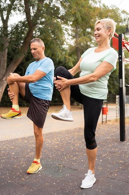 Вид сбоку пожилой пары, разогревающейся перед тренировкой на открытом воздухе Premium Фотографии