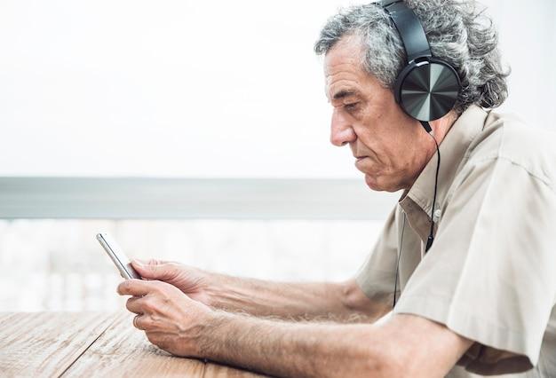 Вид сбоку старшего человека, глядя на мобильный телефон, слушать музыку на наушники Бесплатные Фотографии