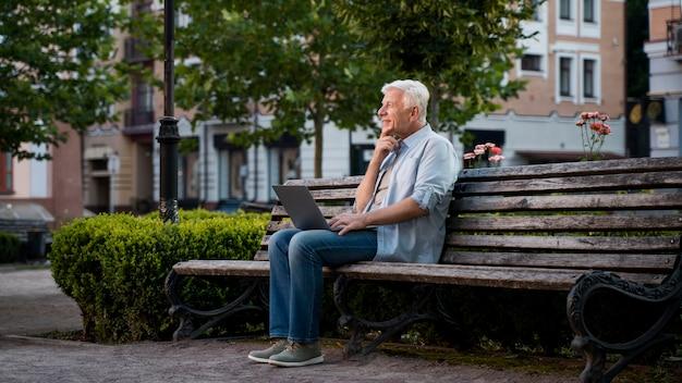 Вид сбоку старшего мужчины на открытом воздухе на скамейке с ноутбуком Бесплатные Фотографии