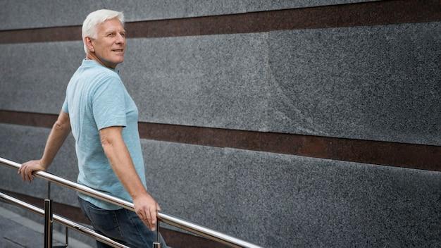 Вид сбоку старшего мужчины, позирующего на открытом воздухе Бесплатные Фотографии
