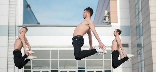 Вид сбоку без рубашки артистов хип-хопа, позирующих в воздухе во время танца Бесплатные Фотографии
