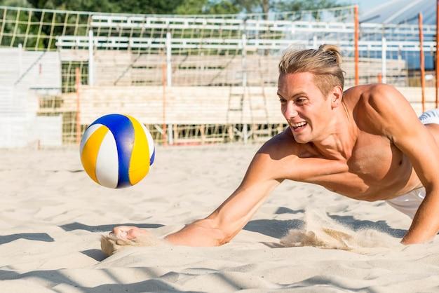 それが砂を打つ前にバレーボールを打つために達する上半身裸の男の側面図 無料写真