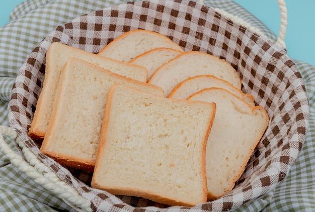 Вид сбоку нарезанный белый хлеб в корзине на клетчатой ткани и синий Бесплатные Фотографии