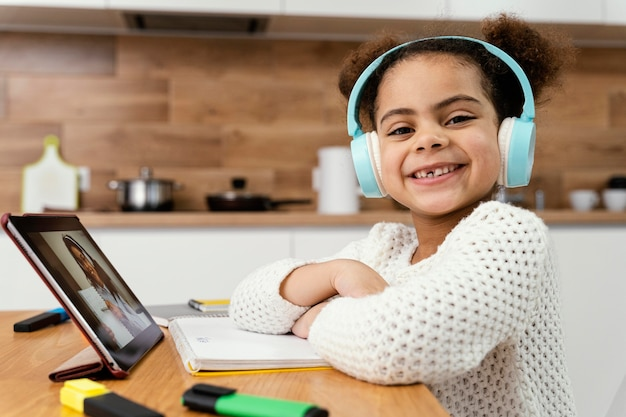 태블릿 및 헤드폰 온라인 학교 동안 웃는 어린 소녀의 측면보기 무료 사진