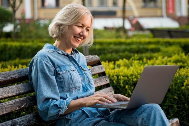 Вид сбоку смайлика пожилой женщины на открытом воздухе на скамейке с ноутбуком Бесплатные Фотографии