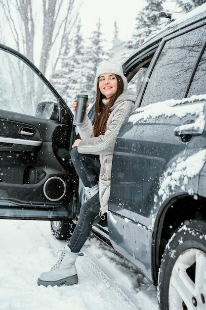Вид сбоку смайлика женщины, наслаждающейся снегом во время поездки и с теплым напитком Бесплатные Фотографии