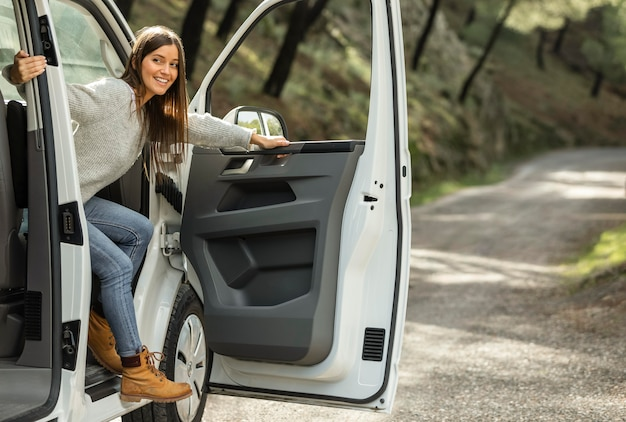 ロードトリップ中に車から降りる笑顔の女性の側面図 無料写真