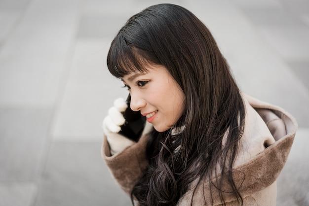 Смайлик женщина разговаривает по телефону на открытом воздухе, вид сбоку Premium Фотографии