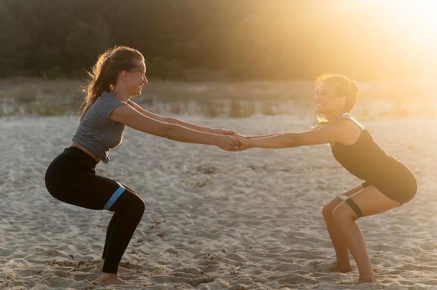 Вид сбоку улыбающихся женщин, работающих вместе на пляже Бесплатные Фотографии