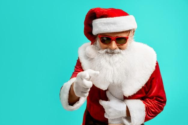 Вид сбоку улыбающийся человек в красном костюме санта-клауса. изолированный портрет старшего мужчины с белой бородой в солнечных очках. концепция праздников. Бесплатные Фотографии