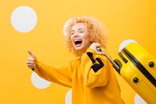 Вид сбоку улыбающейся женщины с чемоданом Бесплатные Фотографии