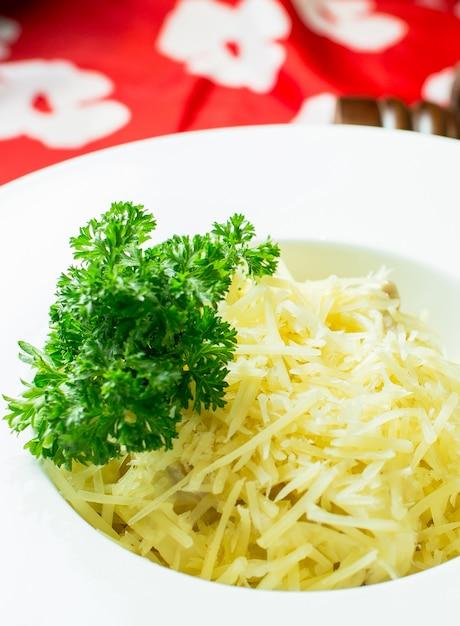 カラフルな白いボウルにパルメザンチーズのミートソースの側面図 無料写真