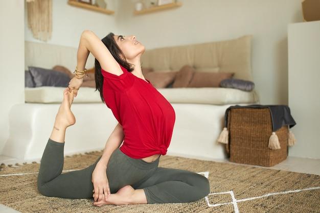 自宅で運動する強い柔軟な体を持つスポーティな裸足の女の子の側面図 無料写真