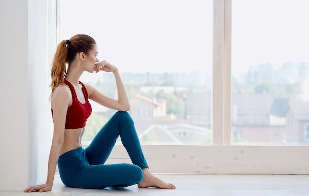 실내 스포츠웨어 창 근처 이상한 여자의 측면보기. 프리미엄 사진