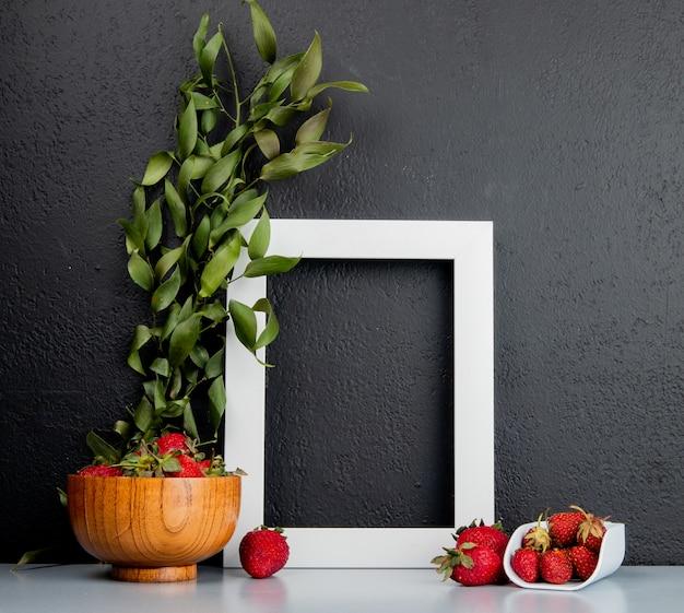 コピースペースを持つ葉で飾られた白い表面と黒の背景上のフレームとボウルにイチゴの側面図 無料写真