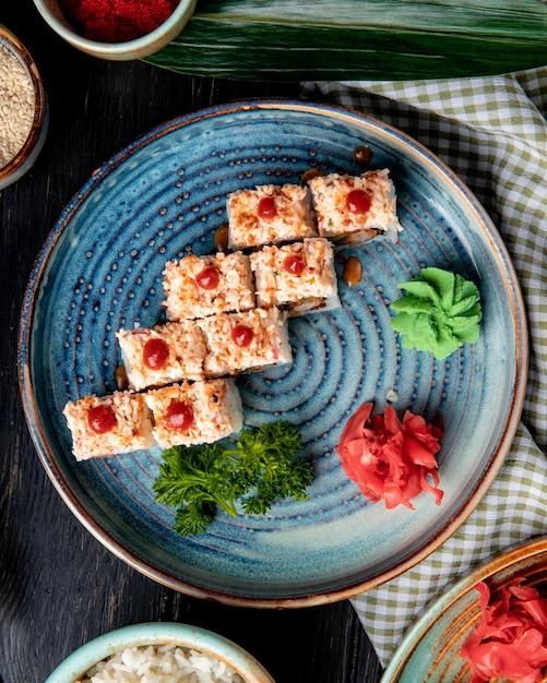 生えび天ぷらアボカドと生姜とわさびのプレートにチーズが入った巻き寿司の側面図 無料写真