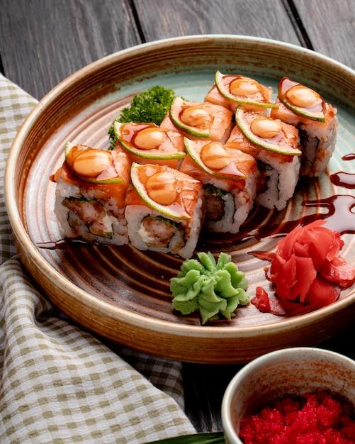 エビのアボカドとクリームチーズの巻き寿司の側面図は、木の皿に生姜とわさびを添えてください。 無料写真