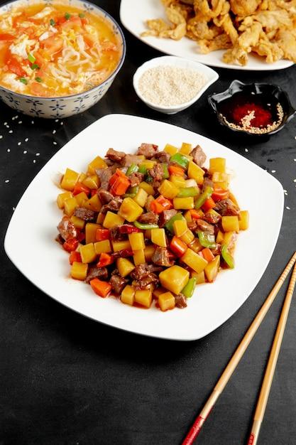 皿に野菜とコショウの甘酸っぱいアヒルの側面図 無料写真