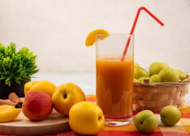 白い背景の上のチェックされたテーブルクロスのバケツに緑の桜の梅と桃ジュースとピンクがかったオレンジ色の桃と木製のキッチンボード上の甘い黄色の桃の側面図 無料写真