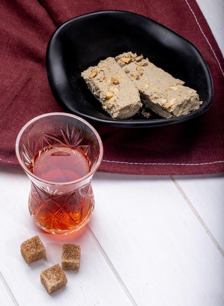 テーブルクロスに黒いボウルと紅茶のアルムドゥグラスでハルヴァのおいしいスライスの側面図 無料写真