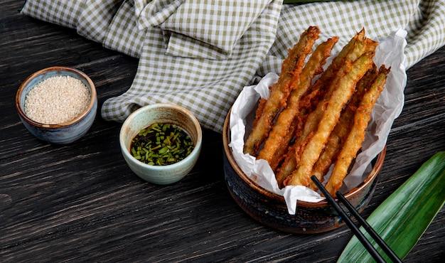 ボウルに天ぷら野菜の側面図チェック柄のファブリックと木製のテーブルの醤油添え 無料写真