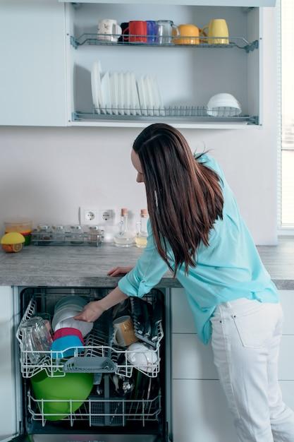 Вид сбоку женщина вытаскивает чистую посуду из посудомоечной машины Premium Фотографии
