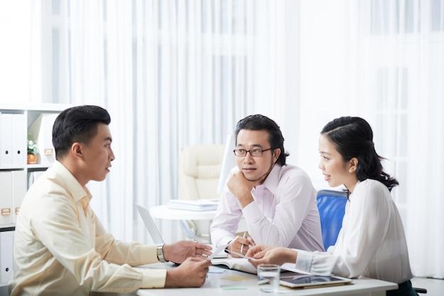 オフィスの机に座ってプロジェクトを議論する3人の同僚の側面図 無料写真