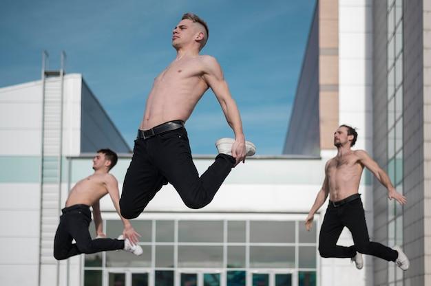 Вид сбоку трех танцоров хип-хопа без рубашки, позирующих в воздухе Бесплатные Фотографии