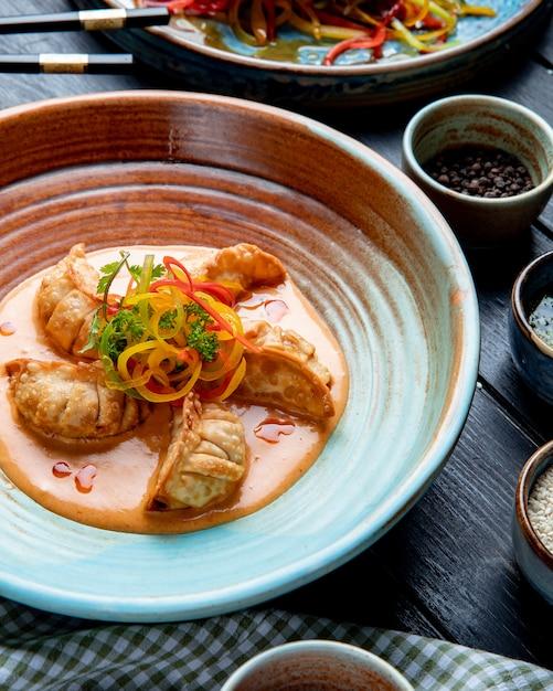 素朴なプレートのソースを添えて肉と野菜の伝統的なアジアの餃子の側面図 無料写真