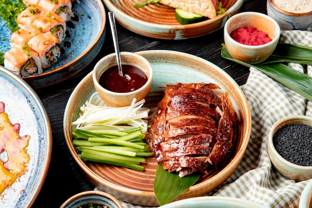 皿の上の伝統的なアジア料理北京ダックきゅうりとソースの側面図 無料写真