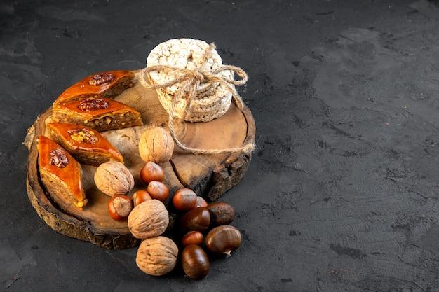 Вид сбоку традиционной азербайджанской пахлавы с орехами рисового хлеба на деревянной доске на черном Бесплатные Фотографии