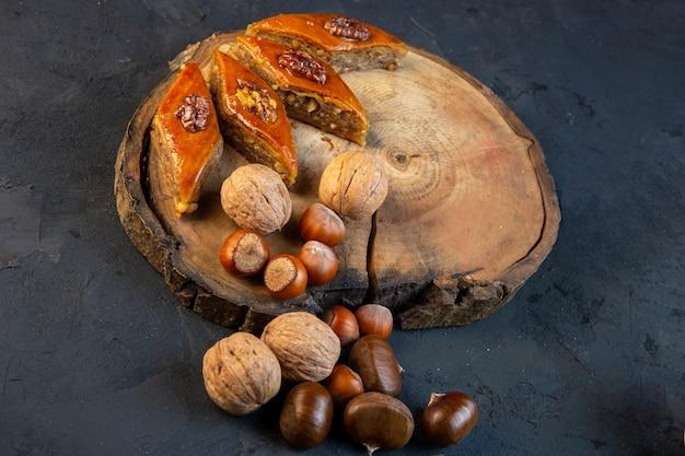 Вид сбоку традиционной азербайджанской пахлавы с целыми орехами на деревянной доске на черном Бесплатные Фотографии