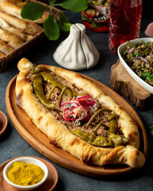 肉と木製の大皿に漬けホットチリピーマンの伝統的なジョージアン料理ハチャプリの側面図 無料写真