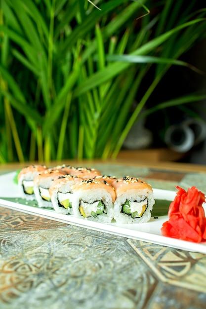 緑のサーモンフィラデルフィアチーズキュウリアボカドと伝統的な日本料理フィラデルフィアロール寿司の側面図 無料写真