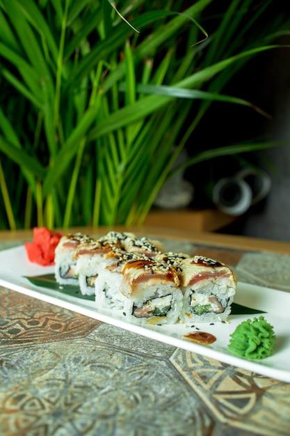 Вид сбоку суши ролл традиционной японской кухни с авокадо угорь и сливочный сыр на зеленый Бесплатные Фотографии