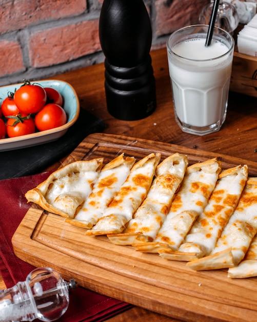 Вид сбоку турецкого пиде с сыром на деревянной разделочной доске Бесплатные Фотографии