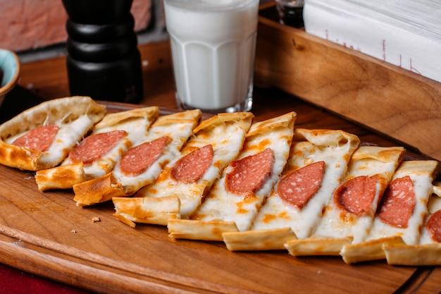 Вид сбоку турецкого пиде с колбасой салями, на деревянной разделочной доске Бесплатные Фотографии