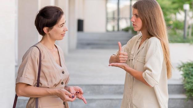 Вид сбоку двух подруг на открытом воздухе, разговаривающих на языке жестов Бесплатные Фотографии
