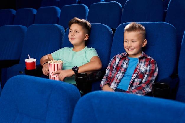 空の映画館で一緒にコミカルな映画を見て笑顔の2人の男の子の側面図です。ポップコーンと甘い水を保持している男性の友人。笑って週末に休む子供たち 無料写真