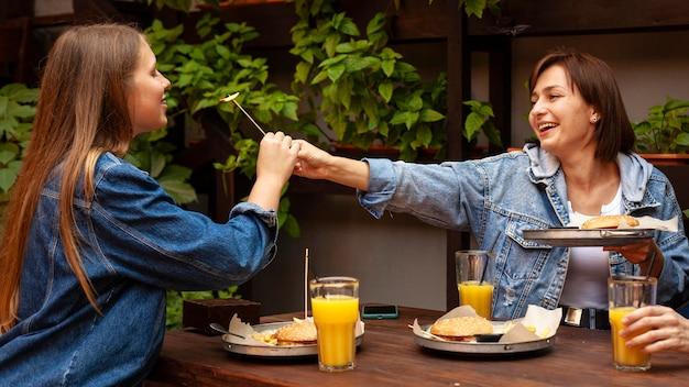 Вид сбоку двух женщин, кормящих друг друга гамбургерами Бесплатные Фотографии