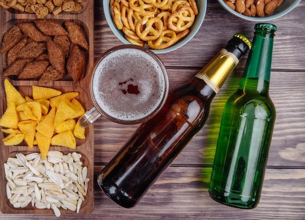 Вид сбоку разнообразных закусок к пиву подсолнечника, хлеб, крекеры, чипсы и мини-крендели с пивом на деревенском Бесплатные Фотографии