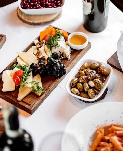 Вид сбоку различных видов сыра с медом и виноградом на деревянной тарелке с маринованными оливками Бесплатные Фотографии
