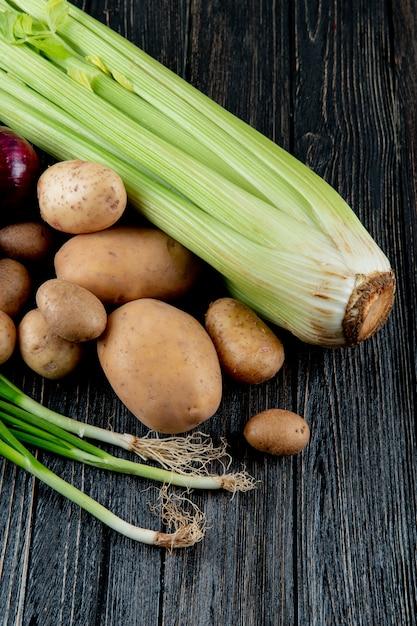 コピースペースを持つ木製の背景にセロリポテトとネギとして野菜の側面図 無料写真